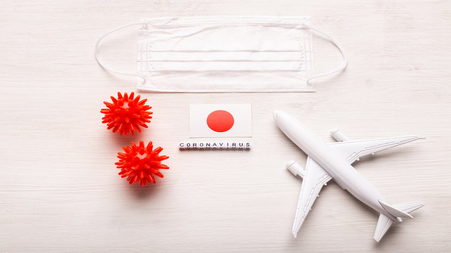 Plane model and face mask and flag Japan. Coronavirus pandemic. Flight ban and closed borders for tourists and travelers with coronavirus covid-19.